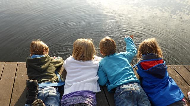 Kinder liegen auf Steg und suchen nach Fischen im Wasser